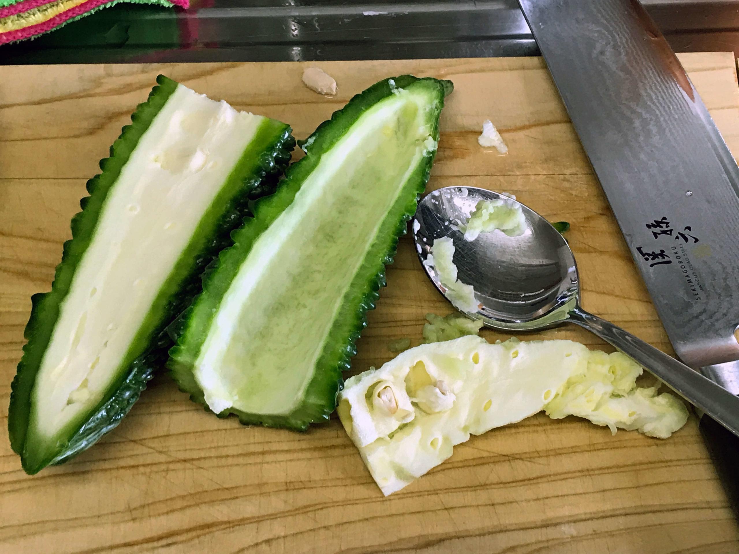 2.ゴーヤーは縦に割り、ワタをスプーンで取り除く。